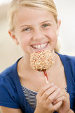 Young girl indoors eating candy apple Stock Photo