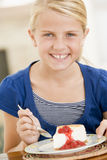 Young girl indoors eating cheesecake. Smiling Royalty Free Stock Image