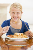 Young girl indoors eating fish and chips. Smiling Royalty Free Stock Photography