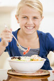 Young girl indoors eating seafood Royalty Free Stock Image