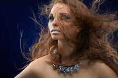 Young girl with intresting make-up. A photo of a beatiful girl with curly, long, dispersing hair and mysterios make-up. She has white lips and pattarns on her Royalty Free Stock Photography