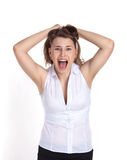 A young girl on an isolated white background screaming in frustration, pulling her hair on her head. Emotional stress Stock Photos