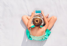 Young girl istening to music from mobile phone. Young girl sitting on a blanket outdoors and listening to music from mobile phone Stock Images