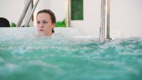 Young girl in jacuzzi, spa procedures in public aqua park. Fist threatening brother stock footage