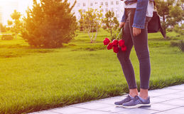 Young girl in jeans with bouquet of tulips flowers and bag walks in park Stock Photography