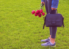 Young girl in jeans with bouquet of tulips flowers and bag walks in park Stock Images