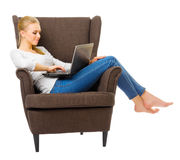 Young girl in jeans on chair with laptop Stock Photo