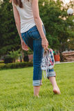 Young Girl in Jeans Holding Sneakers in her Hand royalty free stock photo
