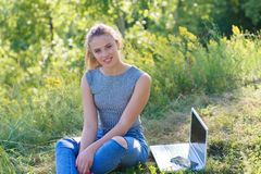 Young girl in jeans in nature sitting on the ground. Next to the girl is a laptop. The girl`s smile royalty free stock photography