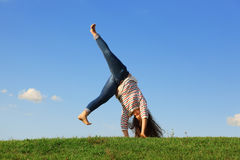 Young girl in jeans tumbles at green grass. At background of blue sky Royalty Free Stock Photos
