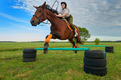 Young girl jockey and her horse jumper. Pretty young girl jockey and her horse jumper Royalty Free Stock Photography
