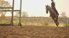 Young girl jockey rides on a horse outdoors.
