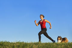 Young girl jogging with a dog Royalty Free Stock Photo