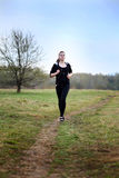 A young girl jogging in a park Stock Photos