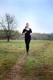 A young girl jogging in a park Stock Photos