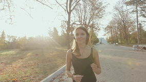 Young girl jogging through the park. And smiling stock video