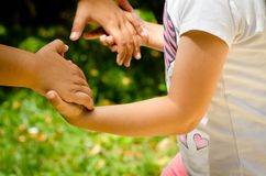 Young girl joining hands with her mother to play. In bright sunny day Royalty Free Stock Image