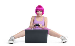 Young girl with joystick sitting on the floor playing games on laptop Royalty Free Stock Image