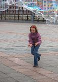 A young girl catches bubbles in the city square. A young girl in a jump catches big soap bubbles on the spring city square stock images