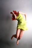 Young girl jumping. Young Caucasian girl leaps into the air Stock Photography