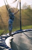 Young girl jumping. Young girl with blond hair jumps on trampoline stock images
