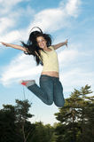 Young girl jumping. Young girl expressing happiness, jumping in the view of the sky Royalty Free Stock Image