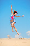 Young girl jumping on a background of blue sky stock image