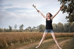 Young girl jumping barefoot on the ground road through field and Stock Image