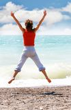 Young girl jumping on beach Royalty Free Stock Photos