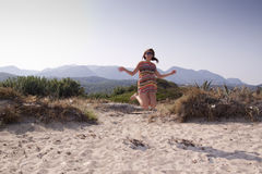 Young girl jumping on the beach Royalty Free Stock Photos