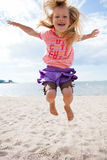 Young girl jumping at beach Stock Image
