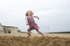 Young girl jumping on a beach. Young girl jumping over a hole on a sandy beach with white chalk cliffs in the distance Royalty Free Stock Images