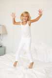 Young Girl Jumping On Bed Stock Image