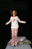 Young girl jumping on the bed Stock Image
