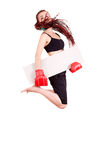 Young girl jumping with boxing gloves and blank card Royalty Free Stock Photography