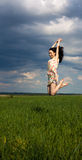 Young girl jumping on the field Royalty Free Stock Photo
