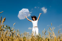 Young girl jumping for joy. Happy young girl jumping for joy with umbrella in the field Royalty Free Stock Images