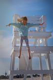 Young girl jumping by lifeguard station Stock Photo