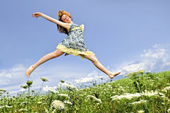Young girl jumping in meadow Stock Image