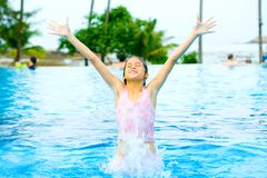 Young girl jumping out of swimming pool. Young girl jumping out of the resort swimming pool Stock Photos