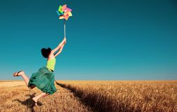 Girl jumping with pinwheel over wheat field royalty free stock photography