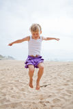 Young girl jumping in sand Royalty Free Stock Photo
