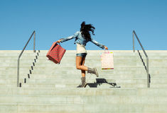 Young girl jumping with shopping bags. Attractive young girl with shopping bags in stairs Royalty Free Stock Photos