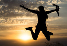 Young girl jumping silhouette with shawl on background of beautiful cloudy sky with yellow sunset Stock Photography