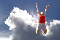 Young girl jumping in sky. Smiling young girl jumping in the air with a sunny Royalty Free Stock Images
