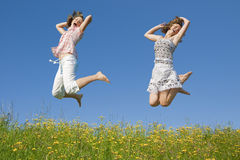 Young girl jumping in sky. Smiling young girl jumping in the air Royalty Free Stock Image