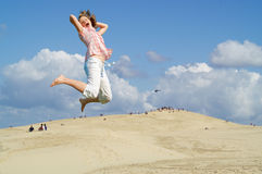 Young girl jumping in sky. Smiling young girl jumping in the air Royalty Free Stock Photography