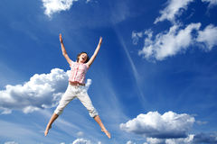Young girl jumping in sky. Smiling young girl jumping in the air Royalty Free Stock Images