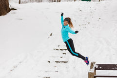 Young girl jumping on the snow. Royalty Free Stock Photos