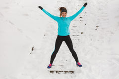Young girl jumping on the snow. Stock Images